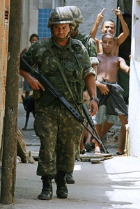 Rio de Janeiro, BRAZIL:  Soldiers patrol a street of the Manguinhos shantytown as resident boys gestures on their backs, 08 March 2006 in Rio de Janeiro, Brazil. Brazilian Army and police forces occupied nine shantytowns in search of ten FAL 7.62mm assault rifles and one 9mm pistol stolen from an army barrack in Rio de Janeiro last Friday.     AFP PHOTO / VANDERLEI ALMEIDA  (Photo credit should read VANDERLEI ALMEIDA/AFP/Getty Images)
