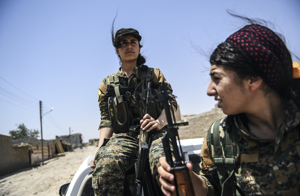 TOPSHOT - Members of the Women's Protection Units (YPJ) arrive on the frontline on the eastern outskirts of Raqa on July 18, 2017, during the ongoing offensive by the Syrian Democratic Forces (SDF), which are made up of an alliance of Kurdish and Arab fighters, to retake the city from Islamic State (IS) group fighters.<br /><br /><br /><br /><br /><br /><br /> The US-backed coalition has captured around 30 percent of Raqa city since it entered the IS bastion in June after a months-long operation to capture territory in the surrounding province. / AFP PHOTO / BULENT KILIC        (Photo credit should read BULENT KILIC/AFP/Getty Images)