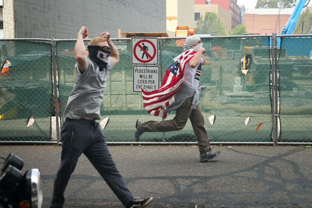 "BERKELEY, CA - APRIL 15: Trump supporters chase after protesters at a ""Patriots Day"" free speech rally on April 15, 2017 in Berkeley, California. More than a dozen people were arrested after fistfights broke out at a park where supporters and opponents of President Trump had gathered. (Photo by Elijah Nouvelage/Getty Images)"