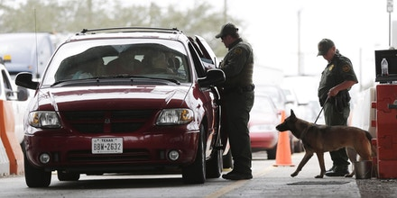 U.S. Customs and Border Patrol agents and K-9 security dog keep watch at a checkpoint station, on Feb. 22, 2013, in Falfurrias, Texas. Some drug smugglers caught at the highway checkpoint about an hour north of the Texas-Mexico border are losing their drugs, but not facing prosecution because cooperation between local and federal prosecutors has broken down. (AP Photo/Eric Gay)