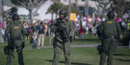 LAGUNA BEACH, CA - AUGUST 20: Sheriff deputies form a line to keep demonstrators and counter demonstrators apart during an 'America First' demonstration on August 20, 2017 in Laguna Beach, California. Organizers of the rally describe it as a vigil for victims of illegal immigrants and refugees. Opponents say the demonstration is steeped in racism.  (Photo by David McNew/Getty Images)