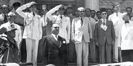 (Original Caption) 7/11/1949-Damascus, Syria- Col. Husni Zaim (center, foreground) stands at attention while the national anthem is played during his recent inauguration in Damascus as President of Syrian republic. Behind him are officers and officials who supported him when he took control of the government in a coup d'etat.