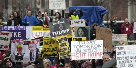 WASHINGTON, DC - JANUARY 20: Protesters demonstrate as President Donald Trump and first lady Melania Trump walk in the inaugural parade after being sworn in at the 58th Presidential Inauguration January 20, 2017 in Washington, DC.  Donald Trump was sworn-in as the 45th President of the United States. (Photo by Kevin Dietsch - Pool/Getty Images)