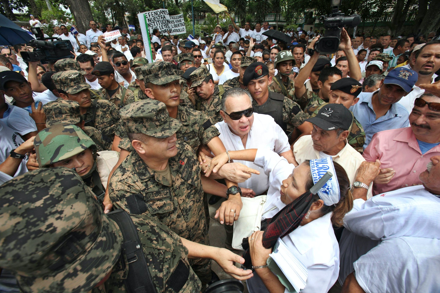 Gen. Romeo Vasquez, center left, head of the Joint Chiefs of Staff fired by Honduras' President Manuel Zelaya late Wednesday for refusing to support a referendum, is greeted by demonstrators during a protest in Tegucigalpa, Friday, June 26, 2009. With backing from Fidel Castro and Hugo Chavez, President Zelaya pushed ahead Friday with a referendum on revamping the constitution, risking his rule in a standoff against Congress, the Supreme Court and the military.(AP Photo/Esteban Felix)