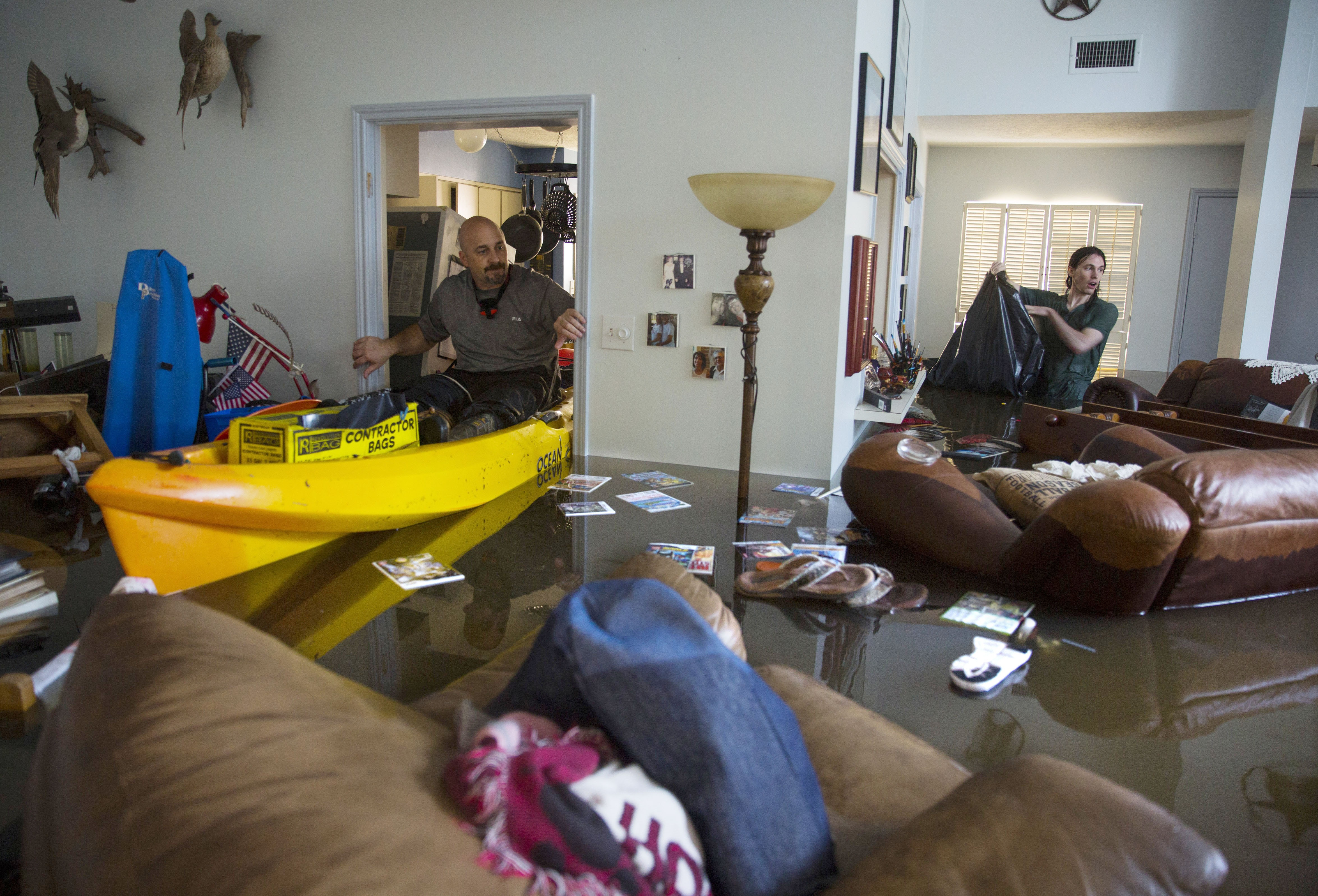 HOUSTON, TX - AUGUST 29:  Larry Koser Jr. (L) and his son Matthew look for important papers and heirlooms inside Larry Koser Sr.'s house after it was flooded by heavy rains from Hurricane Harvey August 29, 2017 in the Bear Creek neighborhood of west Houston, Texas. The neighborhood flooded after water was release from nearby Addicks Reservoir. (Photo by Erich Schlegel/Getty Images)