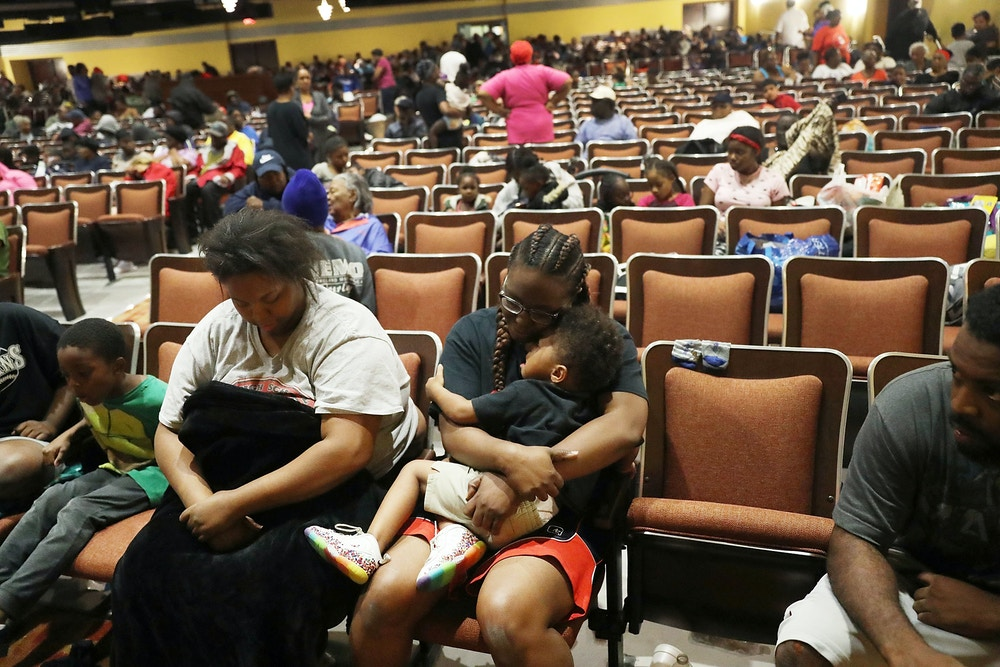 PORT ARTHUR, TX - AUGUST 30:   Evacuees sit in the auditorium of the Woodrow Wilson Middle School after they were evacuated from the flooding of Hurricane Harvey on August 30, 2017 in Port Arthur, Texas. The evacuees said they  were waiting for instructions on where they will sleep for the night as well as when they might be fed. Harvey, which made landfall north of Corpus Christi late Friday evening, is expected to dump upwards to 40 inches of rain in Texas over the next couple of days.  (Photo by Joe Raedle/Getty Images)