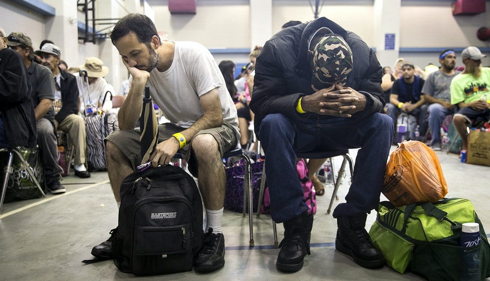 People rest while waiting to board a bus headed for San Antonio at an evacuation center in Corpus Christi, Texas on Friday, Aug. 25, 2017. Hundreds of residents of the Corpus Christi area boarded buses Friday to be transported to a shelter in San Antonio as Hurricane Harvey is expected to make landfall on the Texas coast Friday night or early Saturday morning. (Nick Wagner/Austin American-Statesman via AP)