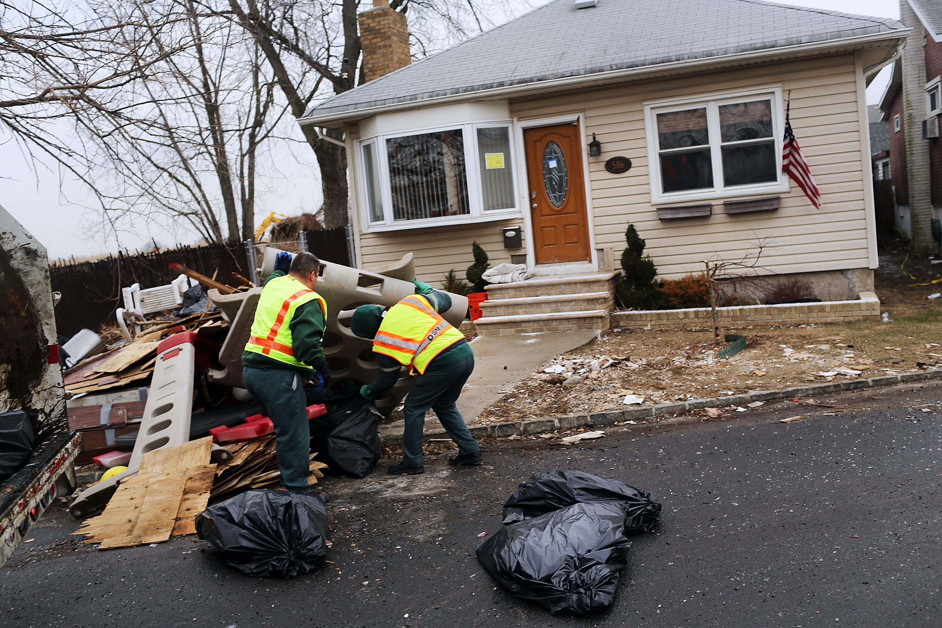 NEW YORK, NY - FEBRUARY 05:  Sanitation workers throw out debris from a flood damaged home in Oakwood Beach in Staten Island on February 5, 2013 in New York City. In a program proposed by New York Governor Andrew Cuomo, New York state could spend up to $400 million to buy out home owners whose properties were destroyed by Superstorm Sandy. The $50.5 billion disaster relief package, which was passed by Congress last month, would be used to fund the program. If the program is adopted, homeowners would be relocated and their land would be left as a natural barrier to help absorb future floods waters.  (Photo by Spencer Platt/Getty Images)