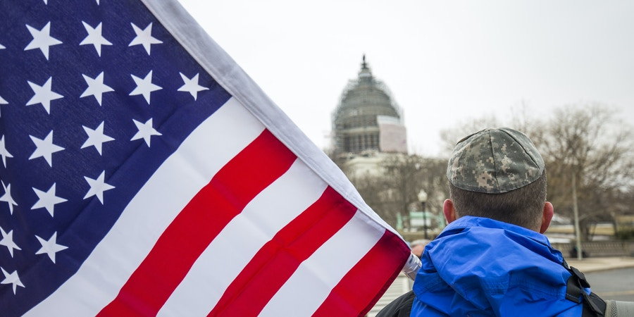 A pro-Israel demonstrator, wearing a military style kipa and holding an American flag, attends a demonstration outside the U.S. Capitol, while Israeli Prime Minister Benjamin Netanyahu addresses a joint session of Congress. (Photo by Brooks Kraft LLC/Corbis via Getty Images)