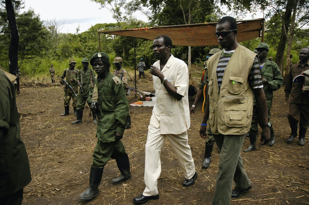 SOUTHERN SUDAN, AUGUST 1:  Joseph Kony, head of the Lords Resistance Army (C), arrives, at a clearing in the  Jungle to take part in peace talks on August 1, 2006 Southern Sudan. At his side is Lft Colonel Steve Ray, a member of the LRA?s high command. He met with delegations representing communities that have been affected by the twenty years war that the LRA has waged against the Ugandan army.  Two day later on August 3, 2006, Kony?s second in charge released a statement via a radio interview that the LRA would not take part in further peace talks without a change of mediation team and a decleration of ceasefire from the Ugandan government. (Photo by Adam Pletts/Getty Images)