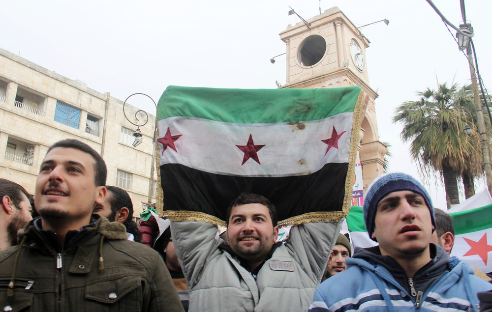 A man holds up a pre-Baath Syrian flag as dozens of people take part in a small gathering calling for the fall of the regime on December 30, 2016, in the northwestern city of Idlib.A nationwide ceasefire is holding across most of Syria but clashes near Damascus underlined the fragility of the deal brokered by Turkey and Russia. / AFP / Omar haj kadour (Photo credit should read OMAR HAJ KADOUR/AFP/Getty Images)