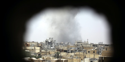 TOPSHOT - Smoke rises from building in Raqa's eastern al-Sanaa neighbourhood, on the edge of the old city, on August 13, 2017, as Syrian Democratic Forces (SDF), a US backed Kurdish-Arab alliance, battle to retake the city from the Islamic State (IS) group.  / AFP PHOTO / Delil souleiman        (Photo credit should read DELIL SOULEIMAN/AFP/Getty Images)
