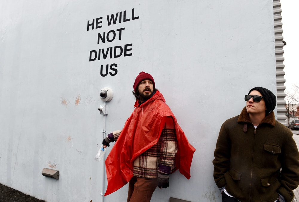 US actor Shia LaBeouf(L)is seen during his He Will Not Divide Us livestream outside the Museum of the Moving Image in Astoria, in the Queens borough of New York January 24, 2017 as a protest against President Donald Trump.<br /><br /><br /><br /><br /><br /><br /><br /><br /><br /><br /><br /><br /><br /><br /><br /><br /><br /><br /> LaBeouf has installed a camera at the Museum of the Moving Image in New York that will run a continuous live stream for the duration of Trumps presidency. LaBeouf is inviting the public to participate in the project by saying the phrase, He will not divide us, into the camera. / AFP / TIMOTHY A. CLARY        (Photo credit should read TIMOTHY A. CLARY/AFP/Getty Images)