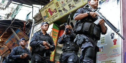 Brazilian BOPE police elite unit personnel patrol during an operation at Rocinha shantytown in Rio de Janeiro, Brazil on April 12, 2013.  AFP PHOTO/VANDERLEI ALMEIDA        (Photo credit should read VANDERLEI ALMEIDA/AFP/Getty Images)