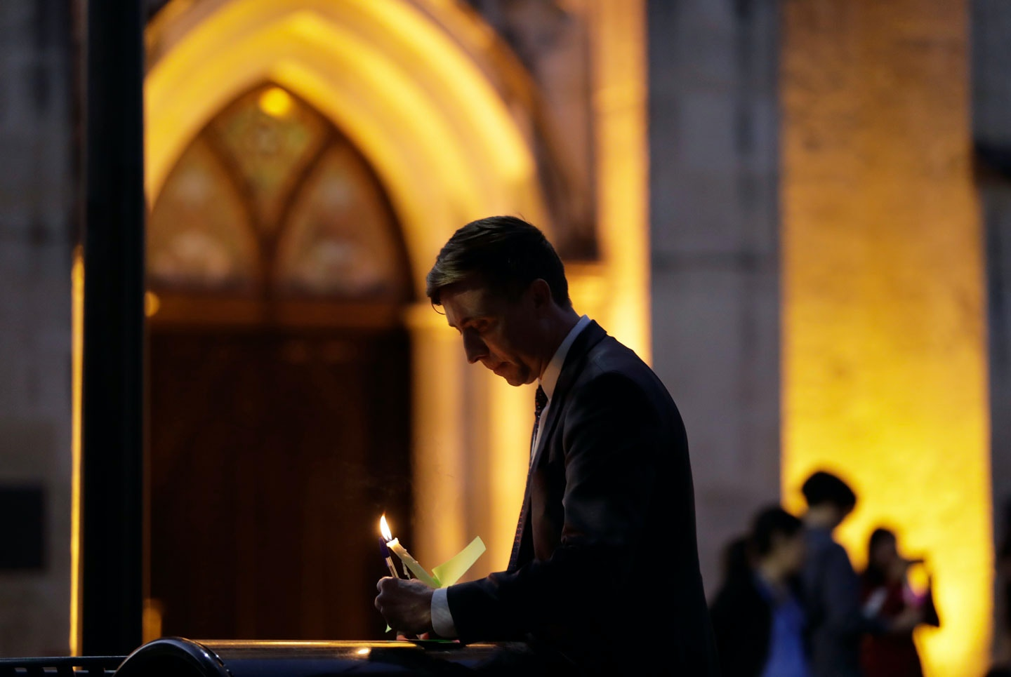Jonathan Ryan writes a note of home as he joins other community activists in front of San Fernando Cathedral for a vigil on the eve of President-elect Donald Trump's inauguration, Thursday, Jan. 19, 2017, in San Antonio. The group gathered to show their support for immigration groups, women's groups, minorities, and others they fear may be harmed by the new administration's policies. (AP Photo/Eric Gay)