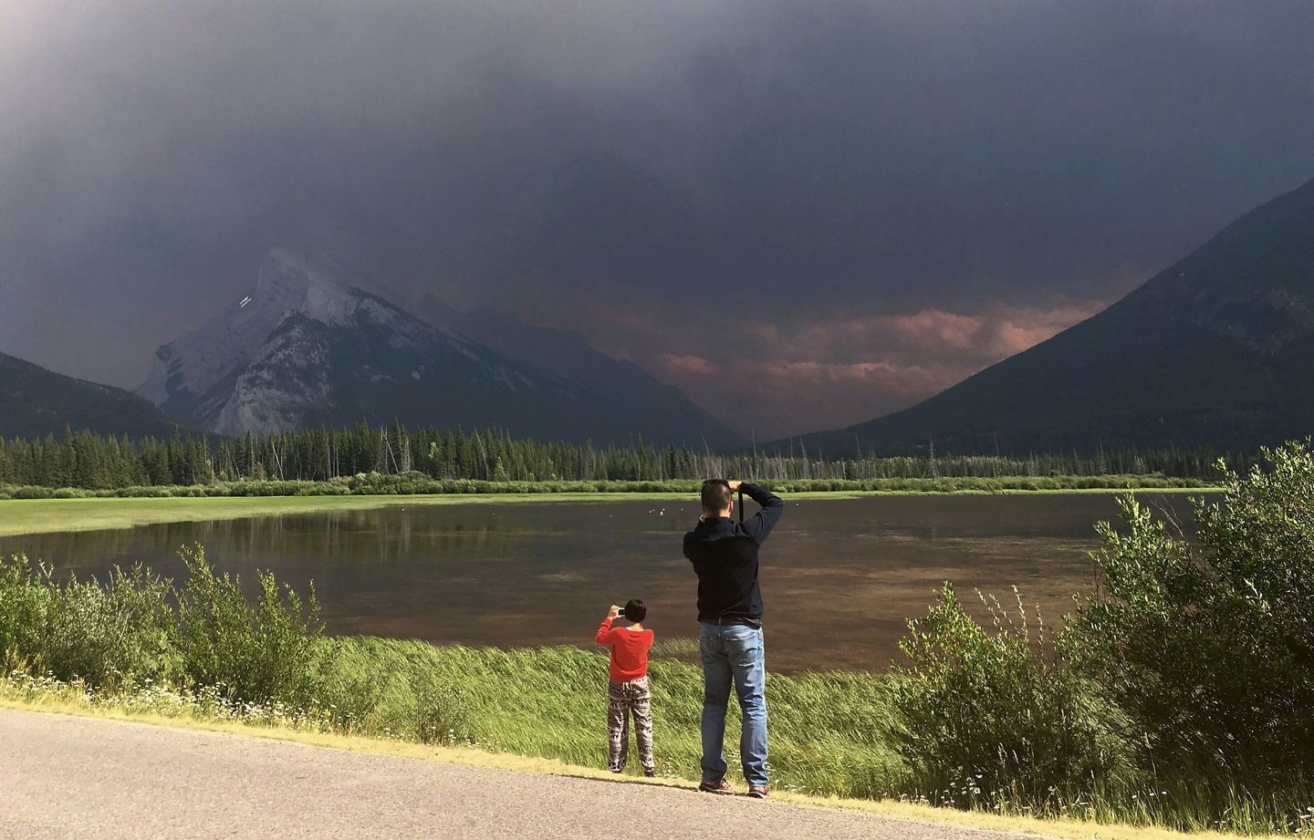 Tourists to Banff National Park in Alberta take photos of Mt. Rundle and the Vermillion lakes as smoke from a forest fire in Kootenay National Park in British Columbia blankets the area, Sunday July 16, 2017. (Adrian Wyld/The Canadian Press via AP)