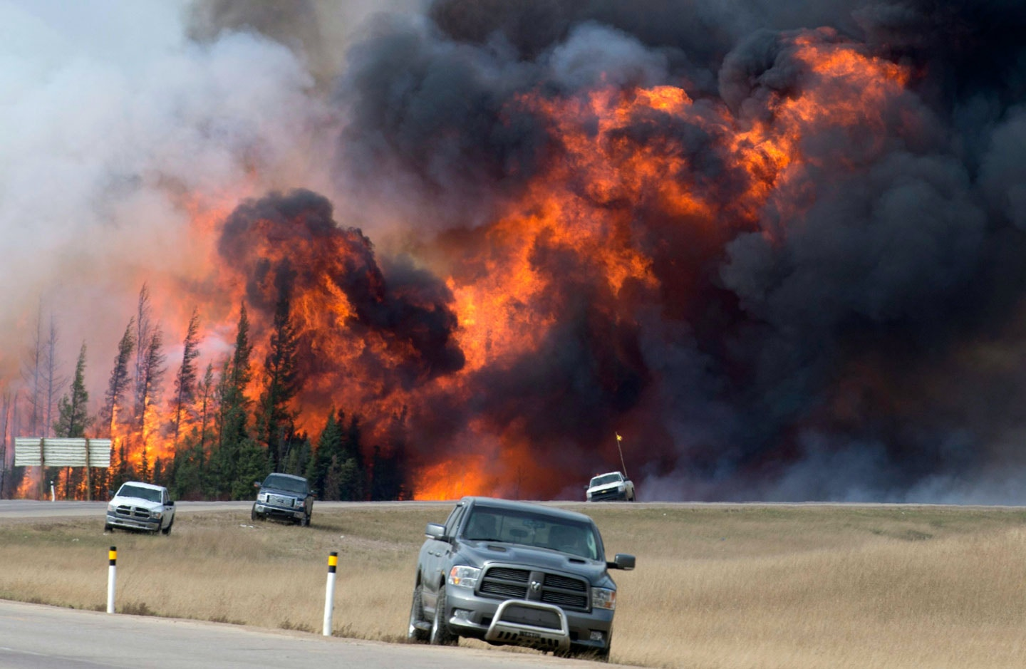 A wildfire burns south of Fort McMurray, Alberta, near Highway 63 on Saturday, May 7, 2016. Canadian officials hoped to complete the mass evacuation of work camps north of Alberta's main oil sands city of Fort McMurray on Saturday, fearing the growing wildfire could double in size and reach a major oil sands mine and even the neighboring province of Saskatchewan.  (Jonathan Hayward /The Canadian Press via AP) MANDATORY CREDIT