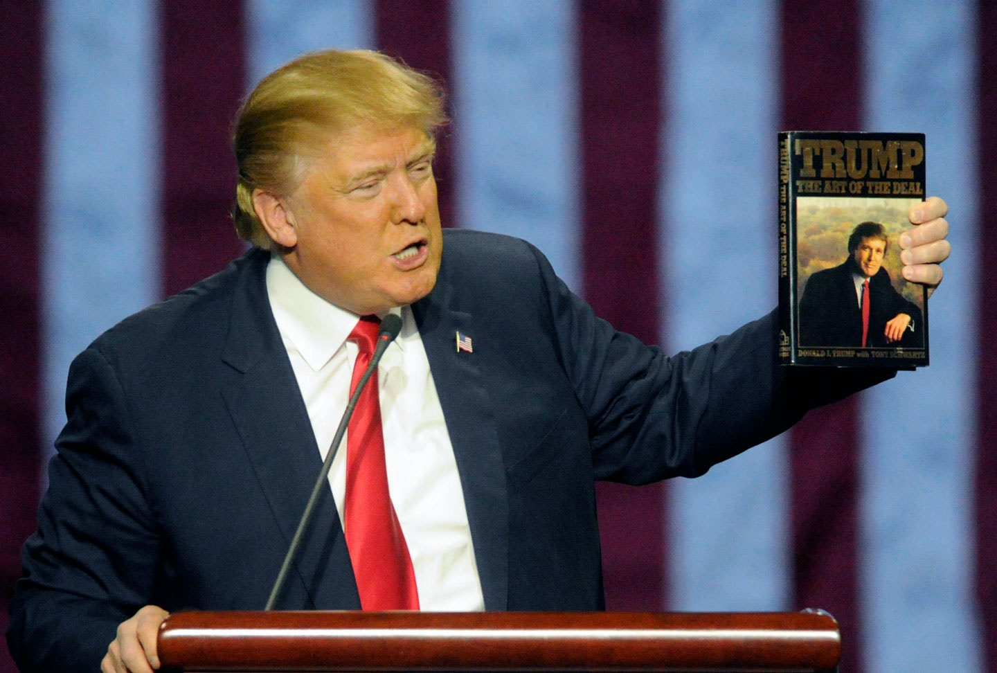 Republican presidential candidate Donald Trump holds up his book 'The Art of the Deal', given to him by a fan as he speaks during a campaign stop Saturday, Nov. 21, 2015 in Birmingham, Ala. (AP Photo/Eric Schultz)