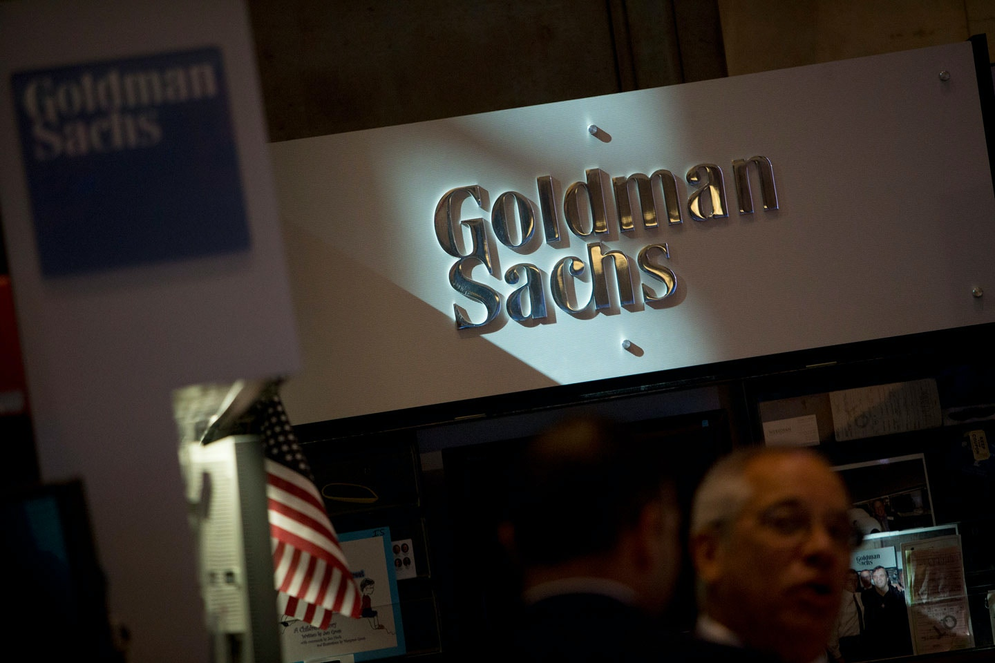The Goldman Sachs & Co. logo is displayed at the company's booth on the floor of the New York Stock Exchange (NYSE) in New York, U.S., on Friday, July 19, 2013. U.S. stocks fell after benchmark equities gauges rose to records yesterday, after disappointing earnings from Google Inc. and Microsoft Corp. overshadowed better-than-forecast results from General Electric Co. Photographer: Scott Eells/Bloomberg via Getty Images