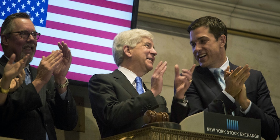 Steve Arwood, chief executive officer of the Michigan Economic Development Corp., from left, Rick Snyder, governor of Michigan, and Thomas Farley, president of NYSE Group Inc., ring the opening bell at the New York Stock Exchange (NYSE) in New York, U.S., on Friday, May 8, 2015. U.S. stocks rose after a rebound in hiring last month bolstered optimism that economic growth is accelerating, but not fast enough to warrant higher interest rates in June. Photographer: Michael Nagle/Bloomberg via Getty Images
