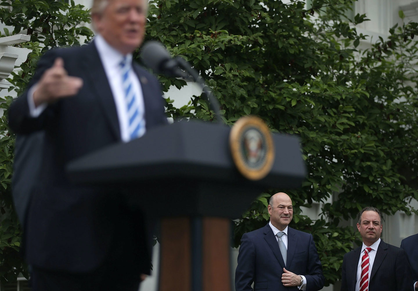 WASHINGTON, DC - MAY 01:  (AFP-OUT) U.S. President Donald Trump speaks to community bankers as Director of the National Economic Council Gary Cohn (2nd R) and White House Chief of Staff Reince Priebus (R) listen druing an event at the Kennedy Garden of the White House May 1, 2017 in Washington, DC. President Trump dropped by and spoke at the event with the Independent Community Bankers Association.  (Photo by Alex Wong/Getty Images)