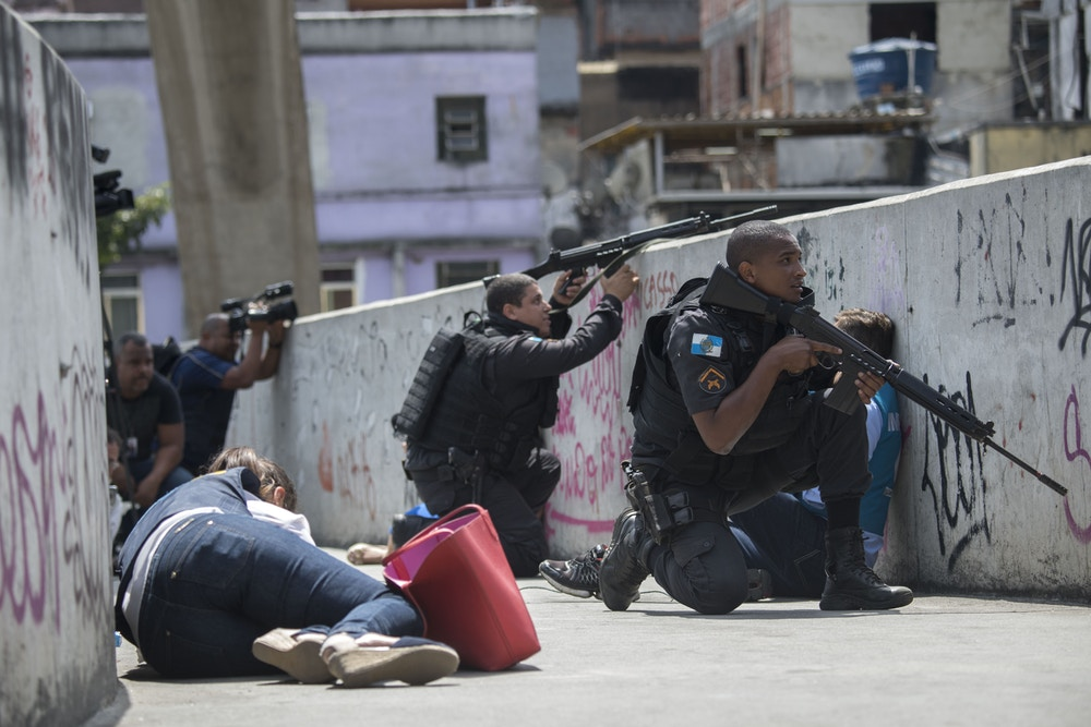 Policemen and journalists take cover during an operation to fight heavily armed drug traffickers at the Rocinha favela in Rio de Janeiro, Brazil, on September 22, 2017. Brazilian soldiers were sent to help Rio de Janeiro police fight heavily armed drug traffickers who have taken over much of the biggest shantytown in the country, the Rocinha favela. Local media reported intense shooting between police and criminals early Friday at Rocinha, where approximately 70,000 people live in a teeming collection of small homes on steep hillsides overlooking western Rio. / AFP PHOTO / Mauro PIMENTEL (Photo credit should read MAURO PIMENTEL/AFP/Getty Images)