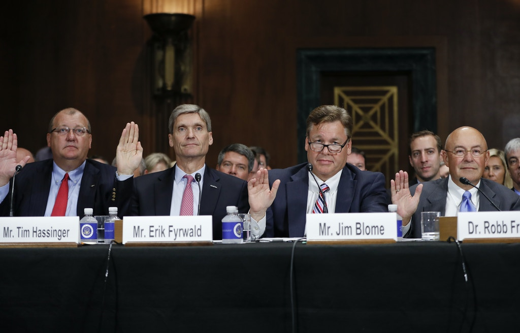 From left, Tim Hassinger , President & CEO, Dow AgroSciences, Erik Fyrwald, Chief Executive Officer, Syngenta International AG, Bayer CropScience North America President and CSO Jim Blome, and Monsanto Company Executive Vice President & Chief Technology Officer Dr. Robb Fraley, raise their right hands to be sworn in, on Capitol Hill in Washington, Tuesday, Sept. 20, 2016, prior to testifying before the Senate Judiciary Committee hearing on a proposed $66 billion merger of American seed and weed-killer company Monsanto and German medicine and farm chemical maker Bayer. (AP Photo/Pablo Martinez Monsivais)