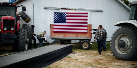 Staff members and volunteers set up the stage at the James Koch Farm in Van Meter, Iowa, October 9, 2012 ahead of US Republican presidential candidate Mitt Romney's arrival for a rally. As the election draws nearer, the press pool and staff member work around the clock in plain sight, as well as behind the scenes, as US Republican Presidential candidate Mitt Romeny travels across the country to deliver his message.       AFP PHOTO/Jim WATSON        (Photo credit should read JIM WATSON/AFP/GettyImages)