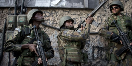 Soldiers take part in a joint operation by the Police and Brazilian Armed Forces to fight heavily armed drug traffickers at the Rocinha favela in Rio de Janeiro, Brazil, on September 22, 2017.Brazilian soldiers were sent to help Rio de Janeiro police fight heavily armed drug traffickers who have taken over much of the biggest shantytown in the country, the Rocinha favela. Local media reported intense shooting between police and criminals early Friday at Rocinha, where approximately 70,000 people live in a teeming collection of small homes on steep hillsides overlooking western Rio. / AFP PHOTO / Mauro PIMENTEL (Photo credit should read MAURO PIMENTEL/AFP/Getty Images)