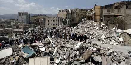 Yemenis stand in protest amidst the debris of a house, hit in an air strike on a residential district, in the capital Sanaa on August 26, 2017.Children were among at least 14 people killed in an air strike that toppled residential blocks in Yemen's capital Sanaa on Friday, witnesses and medics said. / AFP PHOTO / MOHAMMED HUWAIS (Photo credit should read MOHAMMED HUWAIS/AFP/Getty Images)