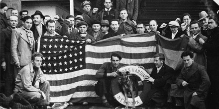 A group of Americans known as  the Abraham Lincoln Brigade, returning from fighting fascists in Spain, pose with the flag and their mascot on the deck of the S.S. President Harding, Feb. 4, 1939. (AP Photo/Fred H. Mann)