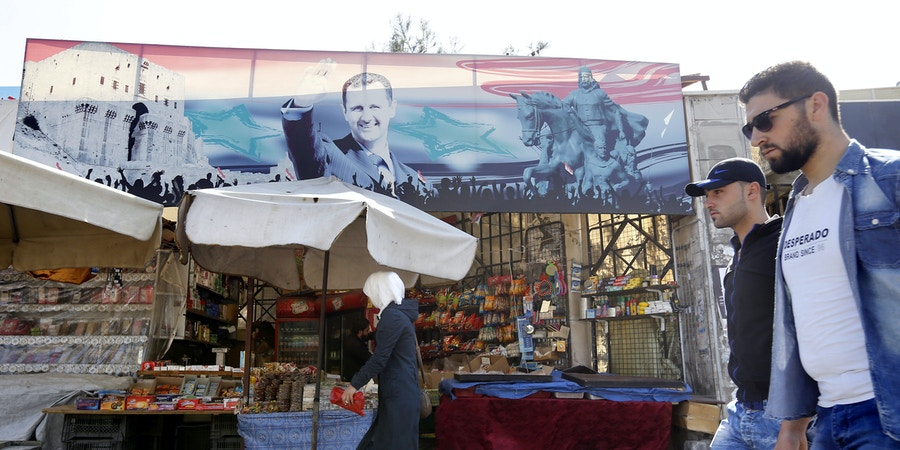Syrians walk past a portrait of Syrian President Bashar al-Assad in Damascus on April 7, 2017.US forces fired a barrage of cruise missiles at a Syrian airbase in response to what President Donald Trump called a