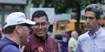 Illinois state senator and candidate for governor Daniel Biss (R) and running mate Carlos Ramirez-Rosa speak with a participant of the Fight for 15 Labor Day march.