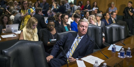 UNITED STATES - SEPTEMBER 25: Sen. Lindsey Graham, R-S.C., waits to testify as protesters disrupt a Senate Finance Committee hearing in Dirksen on the proposal by Graham and Sen. Bill Cassidy, R-La., to repeal and replace the Affordable Care Act on September 25, 2017. The hearing went into recess while the Capitol Police cleared the room. (Photo By Tom Williams/CQ Roll Call) (CQ Roll Call via AP Images)
