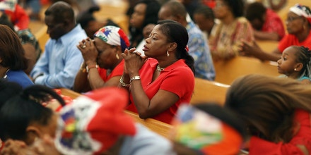 MIAMI, FL - MAY 18:  Parishioners pray together during a service at the Notre Dame D'Haiti Catholic Church as they celebrate Haitian Flag day in the Little Haiti neighborhood on May 18, 2017 in Miami, Florida. The prayer service also touched on the church's concern about the outcome of the decision on extending the Temporary Protected Status for Haitians living in the United States because it would possibly mean friends and families would be sent back to Haiti. 50,000 Haitians have been eligible for TPS and now the Trump Administration has until May 23 to make a decision on extending TPS for Haitians or allowing it to expire on July 22.  (Photo by Joe Raedle/Getty Images)