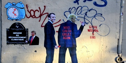 A Street Art work shows US President Donald Trump and President Emmanuel Macron on Paris Climate Agreement in Paris, France on June 13, 2017. Photo by Alain Apaydin/Sipa USA(Sipa via AP Images)