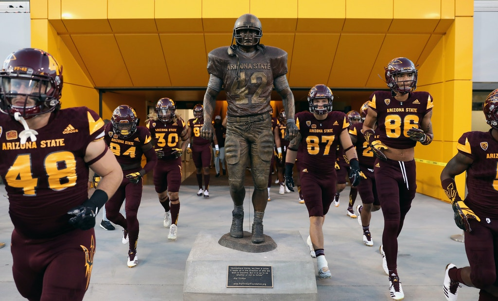 TEMPE, AZ - SEPTEMBER 23:  Arizona State Sun Devils players run past the Pat Tillman statue before the college football game against the Oregon Ducks at Sun Devil Stadium on September 23, 2017 in Tempe, Arizona.  (Photo by Christian Petersen/Getty Images)