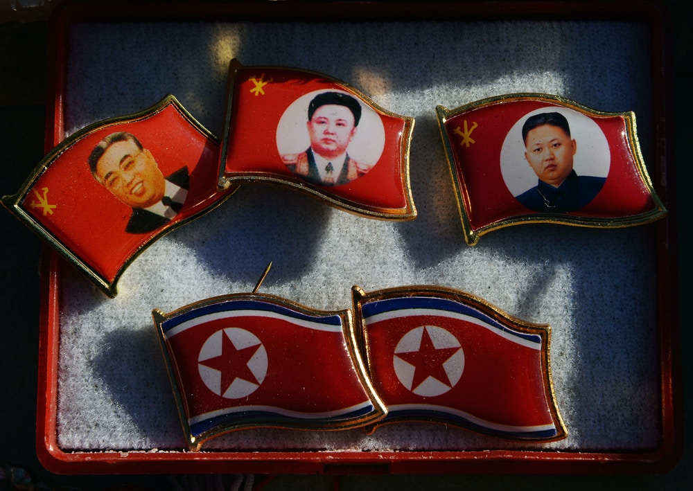 Badges showing late North Korean leaders (L-R) Kim Il Sung and Kim Jong Il and new leader Kim Jong-Un for sale by a street vendor in the Chinese border town of Dandong on the second anniversary of the death of former leader Kim Jong-Il, December 17, 2013.  North Korean leader Kim Jong-Un presided over a major remembrance ceremony on the second anniversary of the death of his father and former leader Kim Jong-Il. The meeting came days after the shock execution of Kim Jong-Un's uncle and one-time political mentor, Jang Song-Thaek -- a purge that raised questions about the stability of the current regime in Pyongyang.        AFP PHOTO/Mark RALSTON        (Photo credit should read MARK RALSTON/AFP/Getty Images)