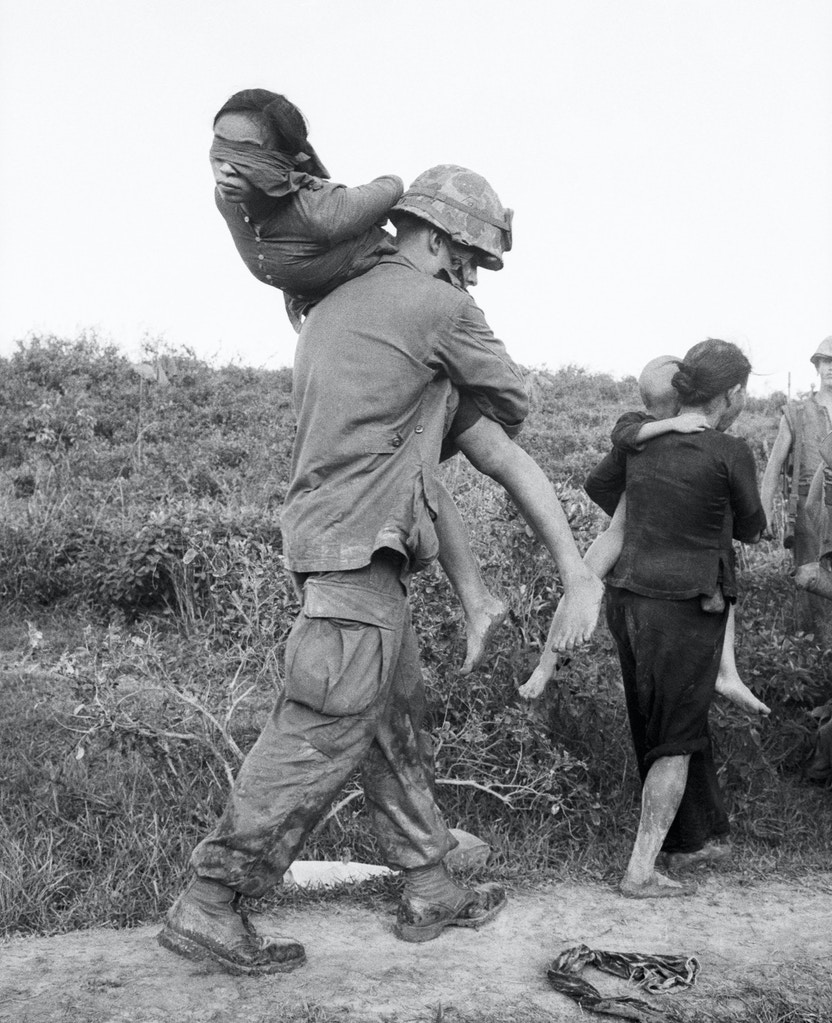 A U.S. Marine carries a blindfolded woman suspected of Vietcong activities. She and other prisoners were rounded up during the joint Vietnamese-U.S. Operation Mallard, near Da Nang, Vietnam.