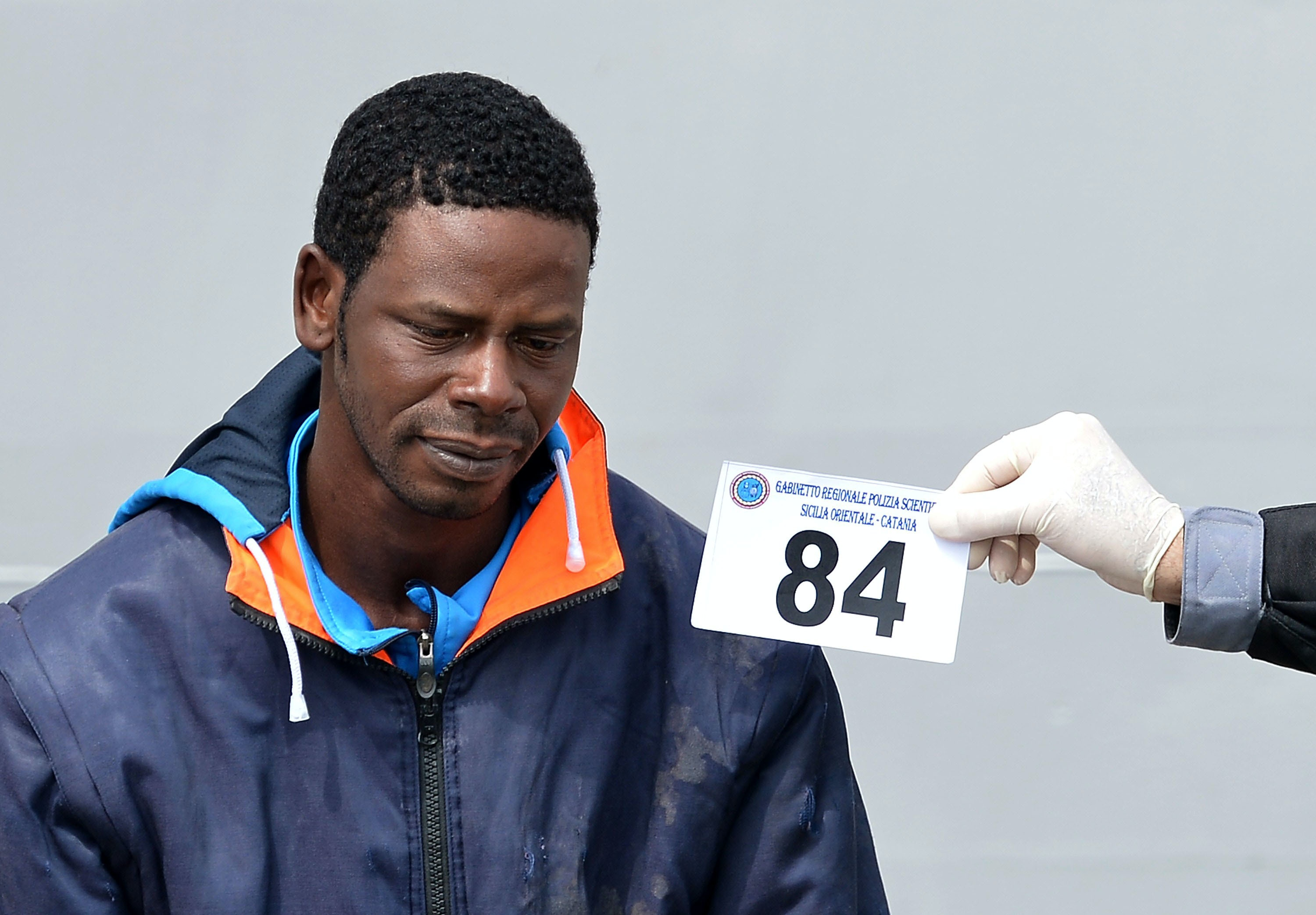 Italian police officers identify a migrant suspected to be a smuggler after disembarking off the Italian Guardia Costiera vessel Fiorillo at the Sicilian harbour of Catania on April 24, 2015. EU leaders gathered in Brussels on April 23 considered launching a military operation against human traffickers in Libya, in a bold effort to halt the deadly flow of refugees trying to reach Europe by sea. AFP PHOTO / ALBERTO PIZZOLI        (Photo credit should read ALBERTO PIZZOLI/AFP/Getty Images)