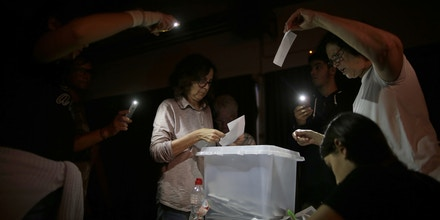 Volunteers, acting as polling station officials, start to count ballots during a blackout after the polling station closed at the La Llacuna school in the Poble Nou neighborhood in Barcelona, Spain, Sunday, Oct. 1, 2017. Spanish riot police, acting on orders from the Spanish government to stop the voting, which Spain's Constitutional Court had declared illegal, smashed their way into Catalan polling stations Sunday to try to halt a disputed referendum on independence.(AP Photo/Manu Fernandez)