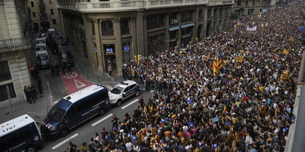 Protesters gather outside the Spanish police headquarters in Barcelona as part of a general strike in Catalonia called by Catalan unions on October 3, 2017.Large numbers of Catalans are expected to observe a general strike today to condemn police violence at a banned weekend referendum on independence, as Madrid comes under growing international pressure to resolve its worst political crisis in decades. / AFP PHOTO / LLUIS GENE (Photo credit should read LLUIS GENE/AFP/Getty Images)