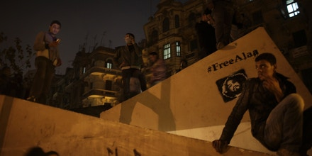 CAIRO, EGYPT - NOVEMBER 22:  Egyptian protesters look on from a raised structure during intense scuffles with police involving rocks, teargas, and molotov cocktails being thrown back and forth in the side streets near Tahrir Square in Cairo, Egypt on November 22, 2011. Graffiti is seen of political activist Alaa Abd El Fattah who was imprisoned the military for