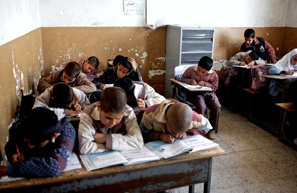 Afghan students attend a class at the Shahid Nasseri refugee camp in Taraz Nahid village near the city of Saveh, some 130 kms southwest of the capital Tehran, on February 8, 2015. Some 5000 Afghan refugees live at the camp which is run by the Iranian Bureau for Aliens and Foreign Immigrants' Affairs (BAFIA), the World Food Program (WFP) and UNHCR. According to the United Nations High Commissioner for Refugees (UNHCR), there are 950,000 registered Afghan residents in Iran -- some of whom have never even set foot in their homeland -- but interior ministry estimates around three million Afghans living in the Islamic republic. AFP PHOTO/BEHROUZ MEHRI        (Photo credit should read BEHROUZ MEHRI/AFP/Getty Images)