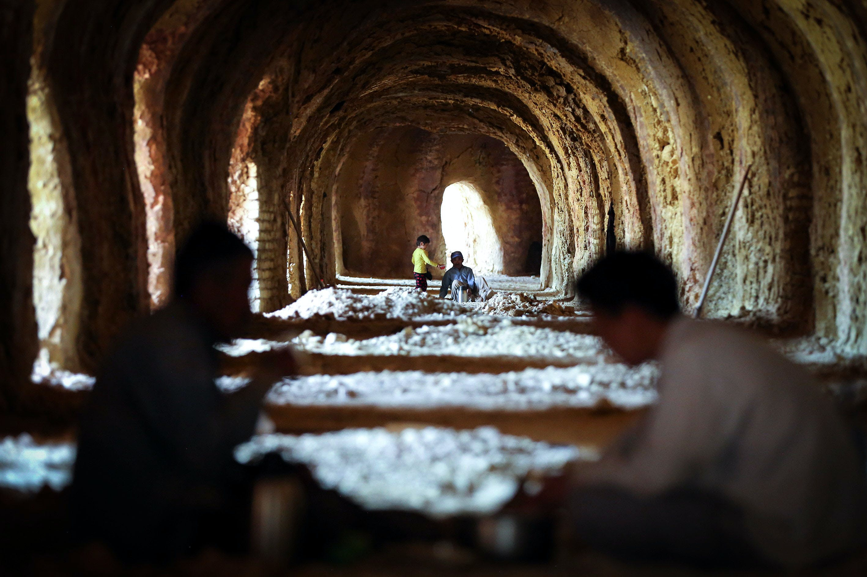 TEHRAN, IRAN - APRIL 24: Afghan immigrants and a child, who migrated to Iran due to security and economic problems in Afghanistan, work approximately 13 hours for 13 dollars daily wage at brick kiln in Pakdasht province of Tehran, Iran on April 24, 2016. (Photo by Fatemeh Bahrami/Anadolu Agency/Getty Images)