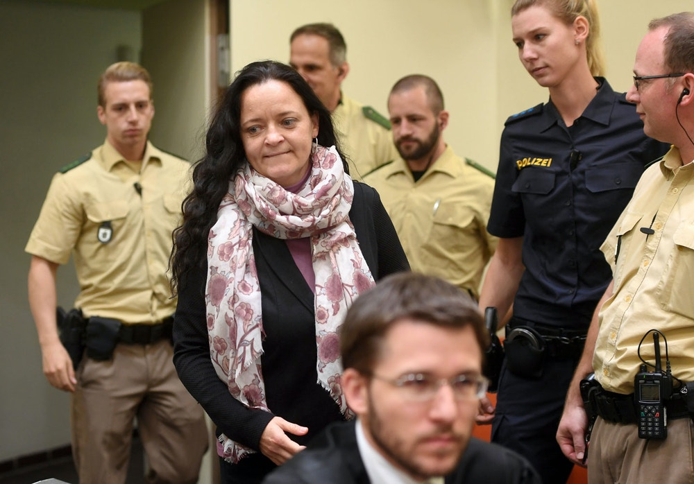 dpatop - Defendant Beate Zschaepe (2.f.l) enters the court room at the Oberlandesgericht court in Munich, Germany, 4 October 2017. Her lawyer Mathias Grasel can be seen in the foreground. Photo by: Tobias Hase/picture-alliance/dpa/AP Images