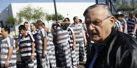 PHOENIX, AZ - APRIL 17:   Inmates walk as they are moved after being ordered by Maricopa County Sheriff Officer Joe Arpaio (R), looking on, to be placed into new housing to open up new beds for maximum security inmates on April 17, 2009 in Phoenix, Arizona. Arpaio has been facing criticism from Hispanic activists and lawmakers, alleging that Arpaio's crackdown methods on illegal immigrants involve racial profiling. (Photo by Joshua Lott/Getty Images)