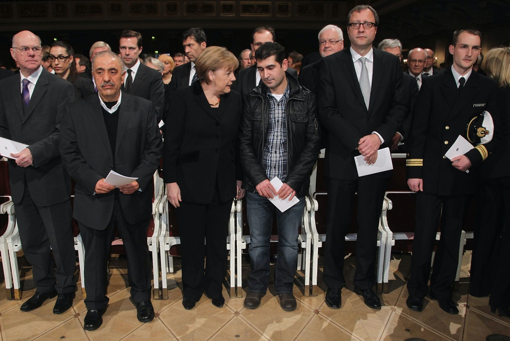 BERLIN, GERMANY - FEBRUARY 23:  German Chancellor Angela Merkel (C) speaks with relatives of victims at a state commemoration for the victims of the NSU neo-Nazi murders at the Konzerthaus am Gendarmenmarkt on February 23, 2012 in Berlin, Germany. German government leaders, state officials and relatives of the victims are commemorating the nine immigrants and one policewoman murdered over a 10-year period in a killing spree by Uwe Mundlos and Uwe Boehnhardt, members of the National Socialist Underground, or NSU, a Neo-Nazi terrorist organization that went undetected by German law enforcement until the two men committed suicide last year after a police chase following a bank robbery. The case has caused a scandal for German law enforcement officials and brought politicians to re-examine the danger of right-wing crime.  (Photo by Sean Gallup/Getty Images)