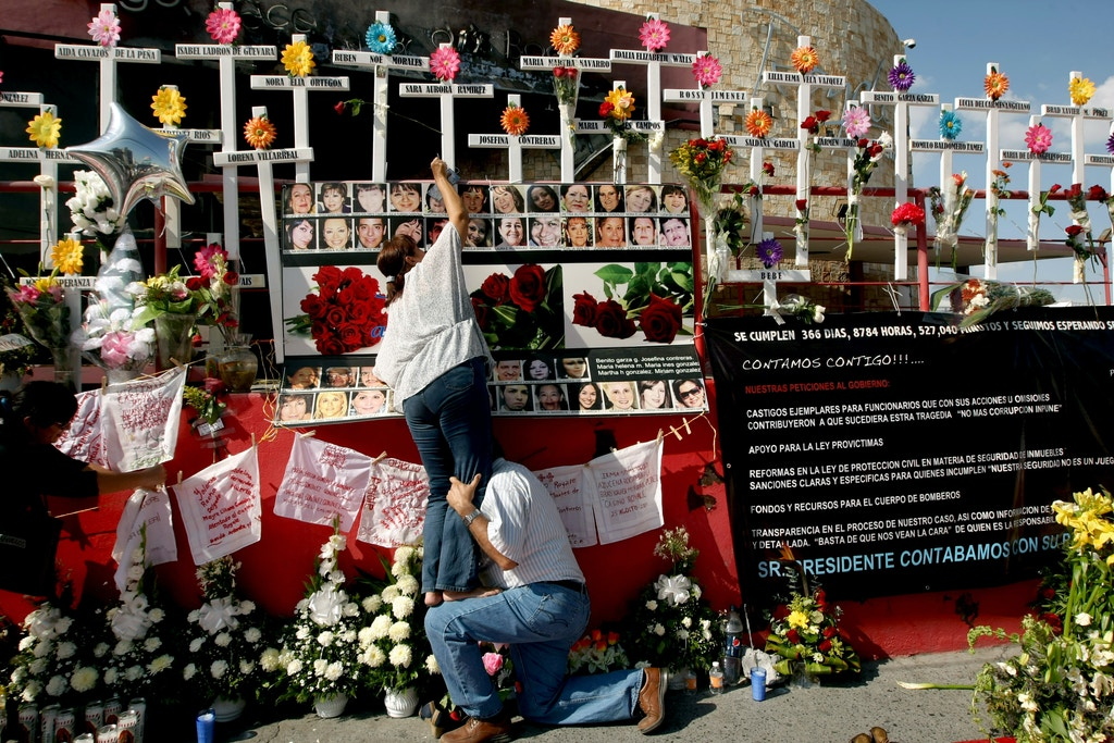 Relativse of victims of the Casino Royale put a flower on a cross during the commemoration of the first anniversary of the crime in Monterrey, Mexico, on August 25, 2012. 52 people died on August 25, 2011, when members of Los Zetas drug cartel doused the Casino Royale with gasoline and set it ablaze. More than 40.000 people have been killed in rising drug-related violence in Mexico since December 2006, when President Felipe Calderon deployed soldiers and federal police to take on organized crime. AFP PHOTO/Julio Cesar Aguilar        (Photo credit should read Julio Cesar Aguilar/AFP/GettyImages)