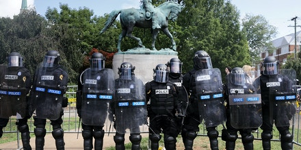 CHARLOTTESVILLE, VA - AUGUST 12:  Virginia State Police in riot gear stand in front of the statue of General Robert E. Lee before forcing white nationalists, neo-Nazis and members of the